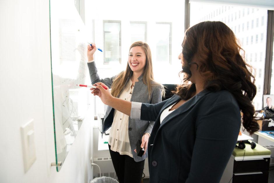Frauen sprechen über dialogorientiertes Marketing an Whiteboard